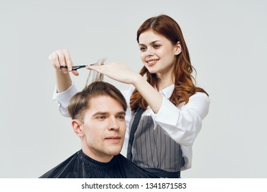woman in gray apron does her hair to a beautiful young man