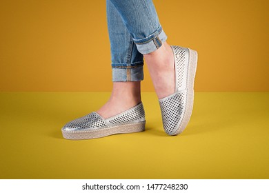 Woman with gray espadrilles on color background