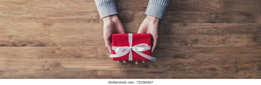 Woman in a gray sweater giving a christmas or birthday gift wrapped in red paper and white ribbon on a wooden table - top view, panoramic web banner with copy space