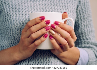 Woman in the gray sweater holding in her hands with a bright nail Polish large white Cup closeup.