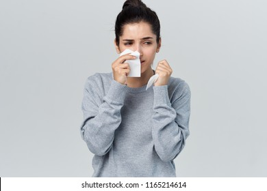 a woman in a gray sweater wipes her face with a napkin