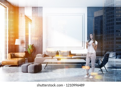 Woman in gray and white wall living room interior with concrete floor, gray and brown sofas, armchair and coffee table with books. Toned image double exposure