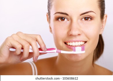 Woman with great teeth holding tooth-brush, isolated on white background