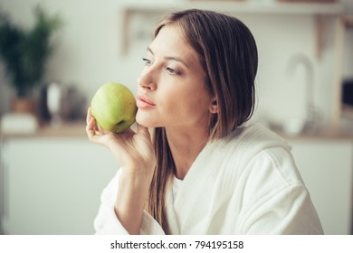 Woman with green apple on kitchen in bathrobe