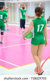Woman in green with ball looks at people in gym during volleyball game, back view, playing people out of focus