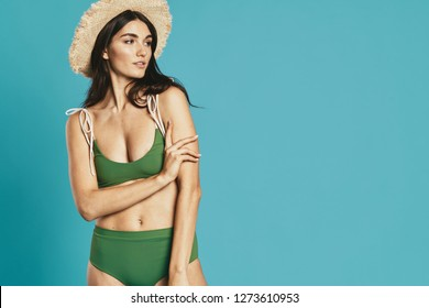 A woman in a green bathing suit and a straw hat on a blue background