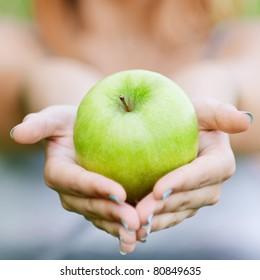 Woman with green big apple, against green summer garden.