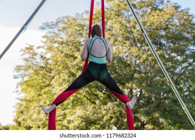 Woman in green and black is attempting a split on red ribbon