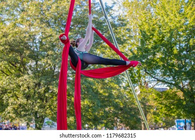 Woman in green and black dance dress does a cross splits on red ribbon