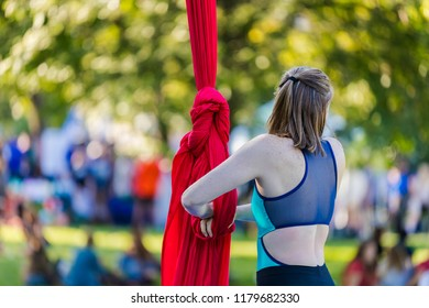 Woman in green and black dance is making knot on red ribbon
