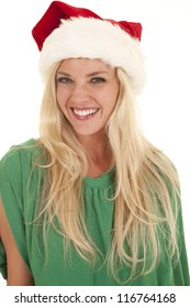 A woman in a green blouse and a santa hat smiling.