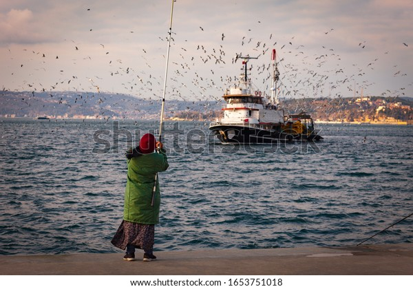woman-green-coat-on-fishing-600w-1653751