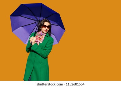 Woman in green coat with purple umbrella on orange background