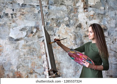 Woman in a green dress in an art studio while drawing on a canvas.