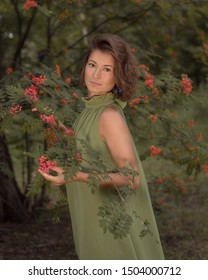 Woman in green dress holds rowan branch in a park or forest. Romantic idea for a book cover, autumn inspitation