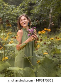 Woman in green dress holds wild flowers bouquet in a park or forest. Romantic idea for a book cover, summer inspitation