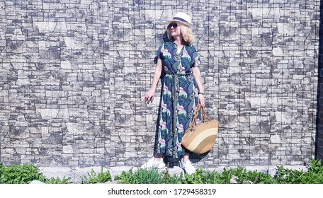 A woman in a green dress with a print is standing against a stone wall.