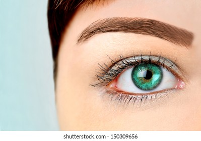 Woman with green eye on blue background