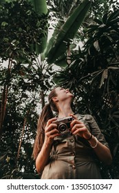 Woman in the green outfit with camera in a jungles among different tropical plants.