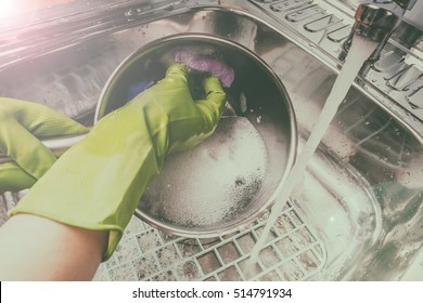 woman in green rubber gloves washing dishes in the sink under water