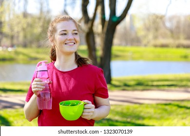 Woman with green salad lunch in the park after workout