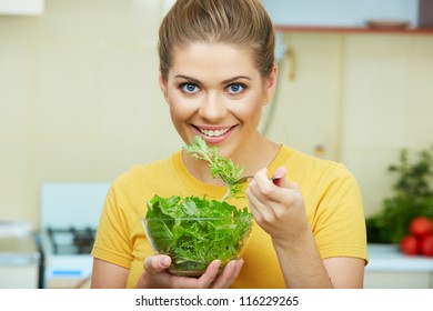 Woman with green salad. Yellow color clothes. Kitchen background.