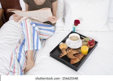 woman green shirt striped pajama pants sitting on white bed reading financial newspaper with breakfast tray croissants orange juice strawberry kiwi cupcake red rose flower