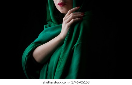 Woman with green veil and red lipstick in black background