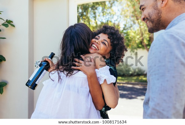 Woman greeting couple for having a new house. Smiling young woman with wine bottle congratulating her friend. Housewarming party with friends.