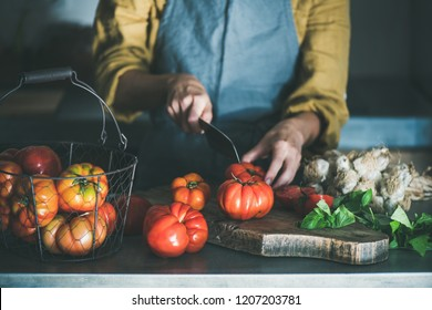 Woman in grey linen apron cooking tomato sauce, canned tomatoes or pasta with heirloom tomatoes, basil and garlic at kitchen counter, horizontal composition. Healthy cooking, slow food or comfort food