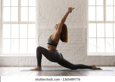 Woman in grey sportswear, bra and leggings practicing yoga, standing in anjaneyasana pose, girl doing Horse rider exercise on mat, working out at home or in yoga studio with white walls