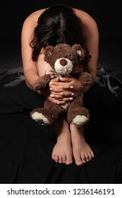 woman in grief holding the teddy bear of an unborn child lost due to miscarriage