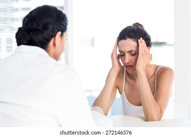 Woman grimacing in front of her doctor in medical office