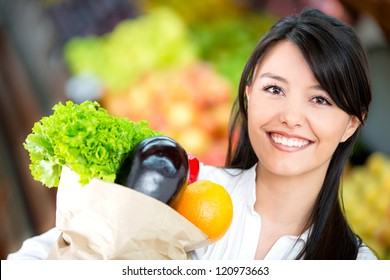 Woman grocery shopping and looking very happy