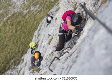 Woman and group of other people climbing on steep rock face on via ferrata. Climbers on via ferrata climbing route. Alpine ferrata ascent to summit. Summer adventure mountain activity.