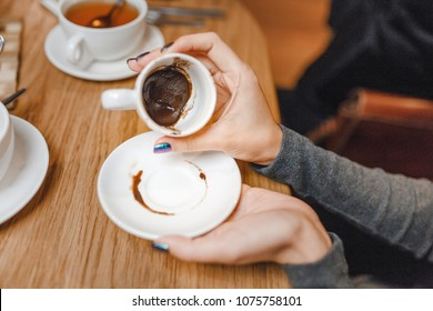 woman guessing on the coffee grounds in restaurant, concept of divination and fortune telling