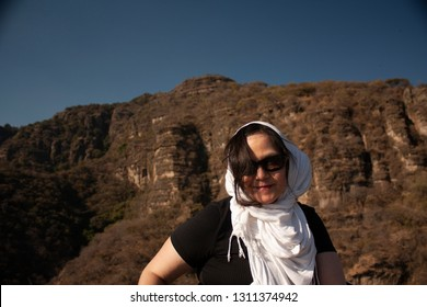 Woman guide working with her head covered by a scarf to protect from the sun's rays, pointing towards the mountain of the speaker in the mountain
