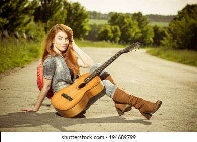 woman with guitar sitting at asphalt road