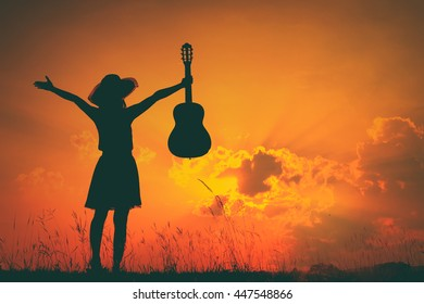 Woman and guitar with sunset silhouette.Summer Vacation concept.Vintage Tone.