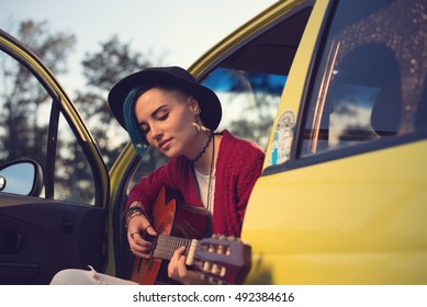 Woman guitarist playing music outdoors