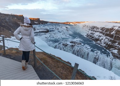 Woman at Gullfoss waterfall Iceland with snow in winter. Dramatic landscape of this majestic waterfall in the Icelandic Golden circle. Travel and nature concepts.