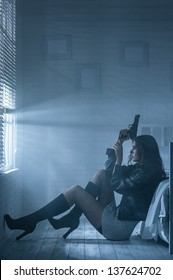 Woman with gun in hand is sitting by the bed in the darkness