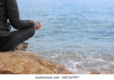 Woman in gyan mudra on the rocks. Sea is the background.