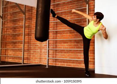 woman in a gym doing leg kicks on sports bag