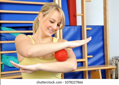 Woman in gym during sports or occupational therapy and exercise with spiky massage ball