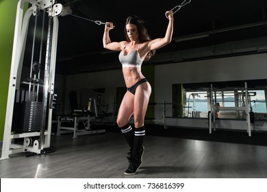 Woman In The Gym Exercising On Her Biceps On Machine With Cable In The Gym