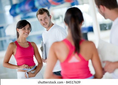 Woman at the gym with her trainer measuring her body