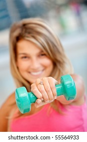 Woman at the gym lifting a free-weight in front of her face and smiling