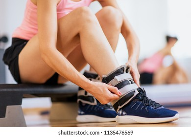 Woman at gym putting ankle weights