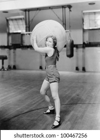 Woman in gymnasium with huge ball